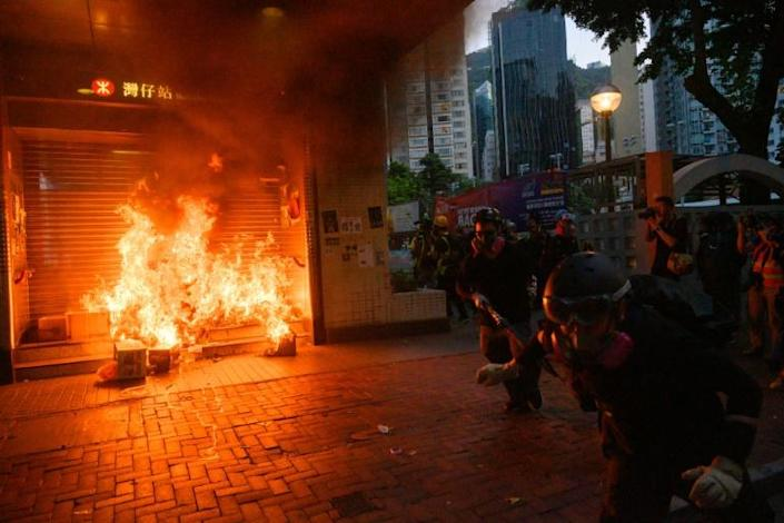 Hong Kong protesters run past a fire at the entrance to a subway station, during clashes with riot police after a rally descended into violence by small groups of hardcore demonstrators (AFP Photo/Anthony WALLACE)