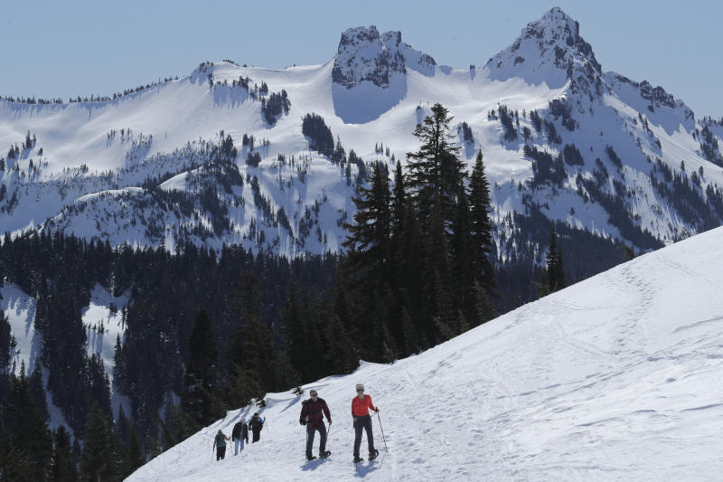 FILE - In this March 18, 2020, file photo, snowshoers head up a slope above Paradise at Mount Rainier National Park in Washington state. As the coronavirus pandemic continues, the National Park Service is testing public access at several parks across the nation with limited offerings and services.  (AP Photo/Ted S. Warren, File)