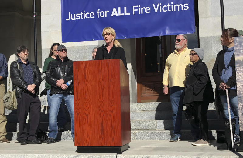 Consumer advocate Erin Brockovich, who famously took on Pacific Gas & Electric Co. in the 1990s, stands with wildfire victims and speaks outside the state Capitol Tuesday, Jan. 22, 2019, in Sacramento, Calif. Brockovich is urging California lawmakers not to let PG&E go bankrupt because it might mean less money for wildfire victims. (AP Photo/Kathleen Ronayne)