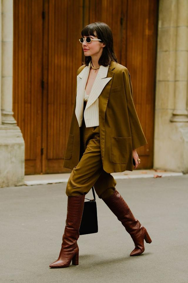 """<p>Put a twist on your classic suit by styling it with a pair of croc-embossed knee-high boots. Tuck your trousers into the boots to really let your footwear shine. </p><p><strong>Get the look: Paris Texas</strong> croc knee-high boots, $795, <a href=""""https://www.modaoperandi.com/paris-texas-pf19/croc-embossed-leather-knee-boots-3?color=brown"""" target=""""_blank"""">modaoperandi.com</a>.</p><p><a class=""""body-btn-link"""" href=""""https://go.redirectingat.com?id=74968X1596630&url=https%3A%2F%2Fwww.modaoperandi.com%2Fparis-texas-pf19%2Fcroc-embossed-leather-knee-boots-3%3Fcolor%3Dbrown&sref=http%3A%2F%2Fwww.harpersbazaar.com%2Ffashion%2Fstreet-style%2Fg6768%2Fwinter-office-outfit-ideas%2F"""" target=""""_blank"""">SHOP NOW</a></p>"""