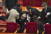 Delegates help former Hong Kong Chief Executive Tung Chee-hwa after he fell following the opening session of China's National People's Congress (NPC) at the Great Hall of the People in Beijing, Friday, March 5, 2021. China's No. 2 leader announced a healthy economic growth target Friday and plans to make this nation self-reliant in technology amid tension with Washington and Europe over trade, Hong Kong and human rights. (AP Photo/Andy Wong)