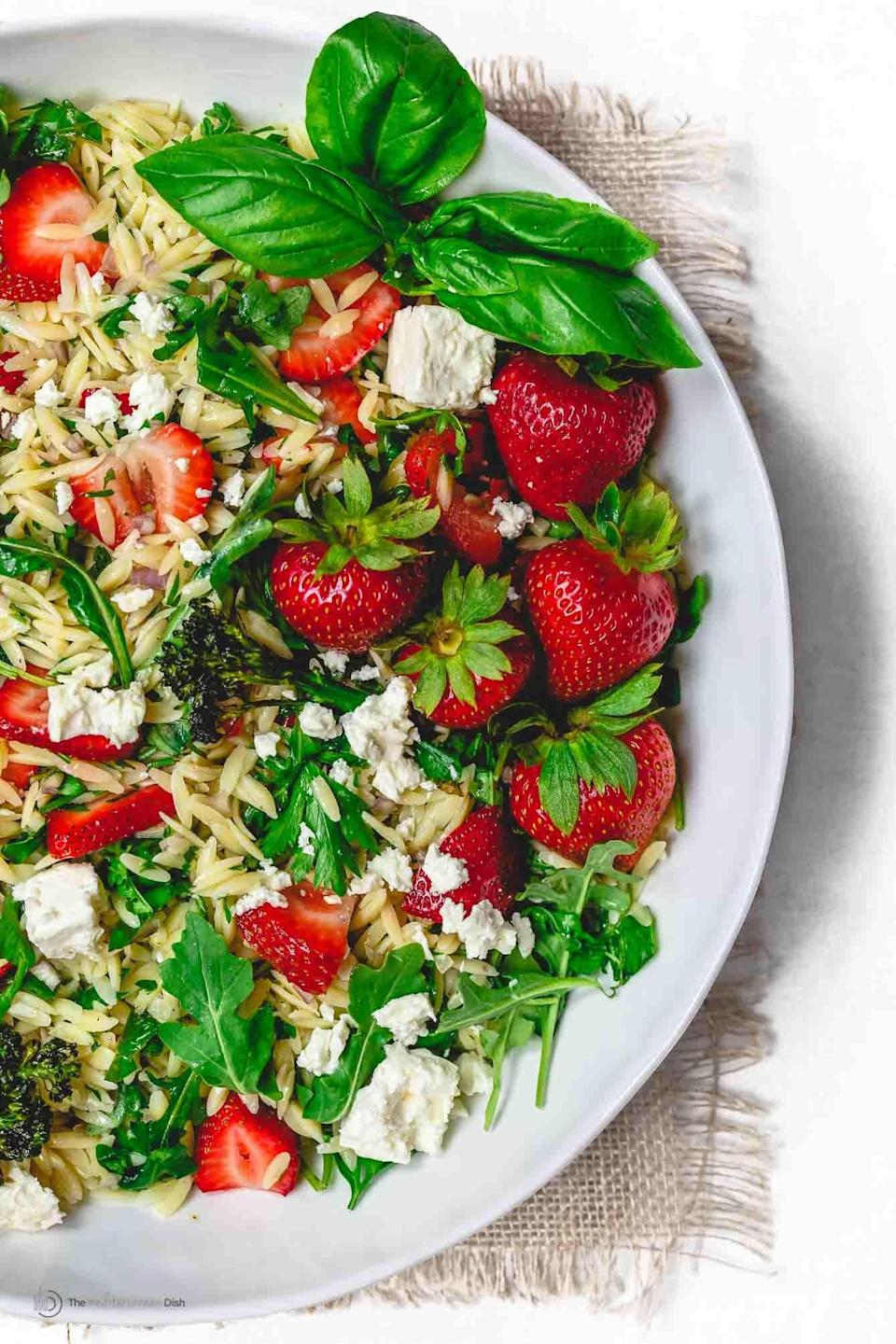 """<p>Bursting with sweet strawberry flavors, this pasta salad tastes like a sunny summer day. We suggest adding bits of mint and goat cheese if you really want to elevate this dish.</p> <p><strong>Get the recipe:</strong> <a href=""""https://www.themediterraneandish.com/mediterranean-strawberry-orzo-pasta-salad/"""" class=""""link rapid-noclick-resp"""" rel=""""nofollow noopener"""" target=""""_blank"""" data-ylk=""""slk:Mediterranean strawberry orzo pasta salad"""">Mediterranean strawberry orzo pasta salad</a></p>"""