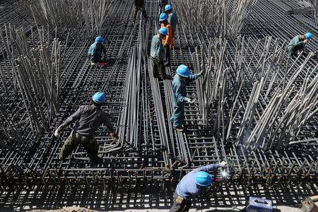 FILE PHOTO: Workers are seen amid steel bars at a construction site of a highway in Zhaotong, Yunnan province, China April 20, 2018. Picture taken April 20, 2018. REUTERS/Stringer/File Photo