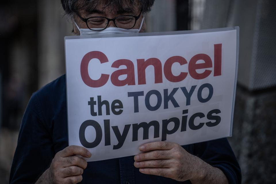 A protester holds a placard during a demonstration against the forthcoming Tokyo Olympic Games on May 23, 2021 in Tokyo, Japan.