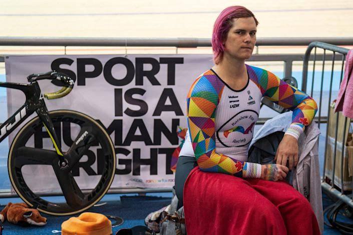 Transgender cyclist Rachel McKinnon sits in front of a bike and signs a book