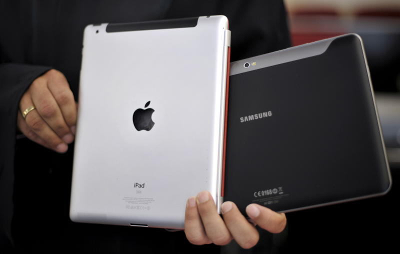 FILE - In this Aug. 25, 2011 file photo, an attorney holds an Apple iPad, left, and a Samsung Galaxy Tab 10.1 at the regional court in Duesseldorf, Germany. The two tech Titans will square off in federal court Monday, July 30, 2012, in a closely watched trial over control of the U.S. smart phone and computer tablet markets. Apple Inc. filed a lawsuit against Samsung Electronics Co. last year alleging the world's largest technology company's smartphones and computer tablets are illegal knockoffs of its popular iPhone and iPad products. (AP Photo/dapd, Sascha Schuermann, File)