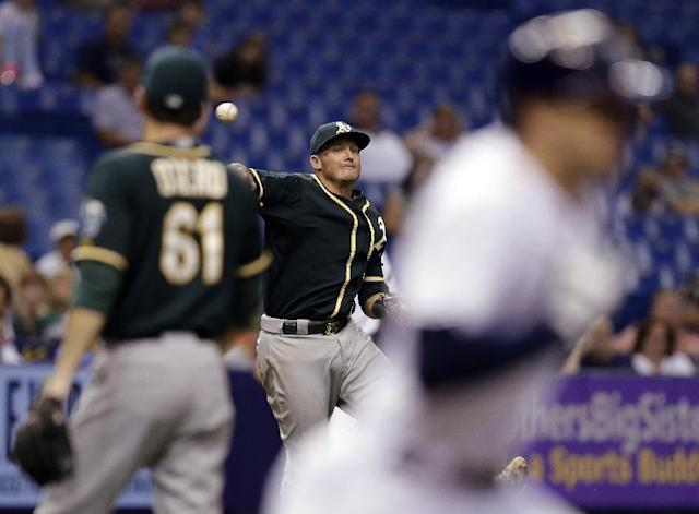 Oakland Athletics third baseman Josh Donaldson, center, throws out Tampa Bay Rays' Evan Longoria, right, at first base on a pitch from Athletics' Dan Otero, left, during the sixth inning of a baseball game Tuesday, May 20, 2014, in St. Petersburg, Fla. (AP Photo/Chris O'Meara)
