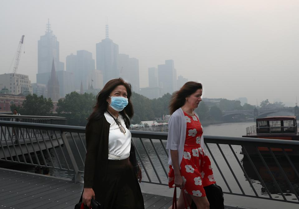 People wear breathing masks to protect themselves from a thick smoke haze that hangs over Melbourne from the bushfires. Source: AAP