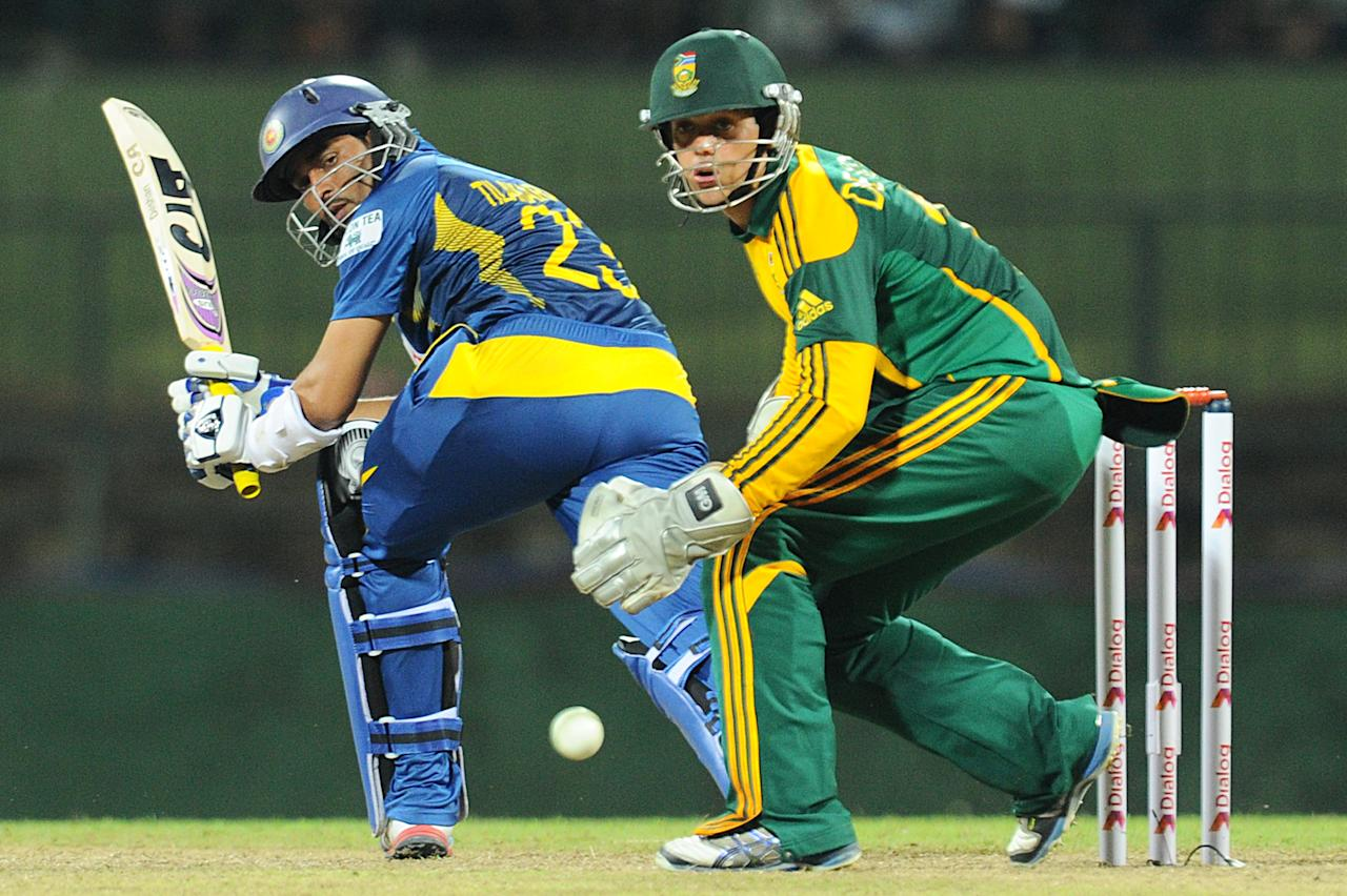 Sri Lankan batsman Tillakaratne Dilshan (L) is watched by South African wicketkeeper Quinton de Kock as he plays a shot during the fourth One Day International (ODI) cricket match between Sri Lanka and South Africa at the Pallekele International Cricket Stadium in Pallekele on July 28, 2013. AFP PHOTO/ Ishara S.KODIKARA