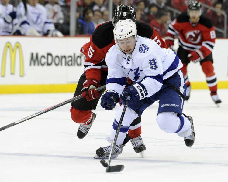 Tampa Bay Lightning center Tyler Johnson (9) breaks away from New Jersey Devils' Adam Larsson during the first period of an NHL hockey game Tuesday, Oct. 29, 2013, in Newark, N.J. (AP Photo/Bill Kostroun)