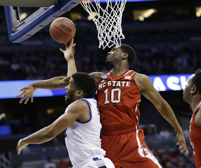 Saint Louis forward Dwayne Evans (21) drives to the basket as North Carolina State forward Lennard Freeman (10) defends during the first half of a second-round game in the NCAA college basketball tournament Thursday, March 20, 2014, in Orlando, Fla. Evans maked the shot. (AP Photo/John Raoux)