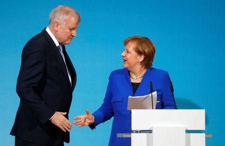 FILE PHOTO - Acting German Chancellor Angela Merkel and leader of the Christian Social Union in Bavaria (CSU) Horst Seehofer shake hands during a news conference after exploratory talks about forming a new coalition government at the SPD headquarters in Berlin, Germany, January 12, 2018.  REUTERS/Hannibal Hanschke