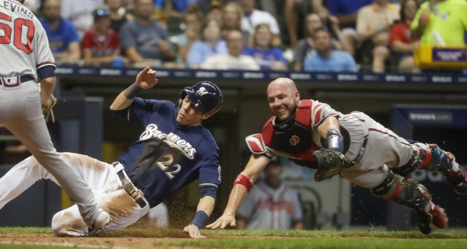 Atlanta Braves catcher Tyler Flowers can't tag Milwaukee Brewers' Christian Yelich as he scores from third on a wild pitch during the fifth inning of a baseball game Tuesday, July 16, 2019, in Milwaukee. (AP Photo/Morry Gash)