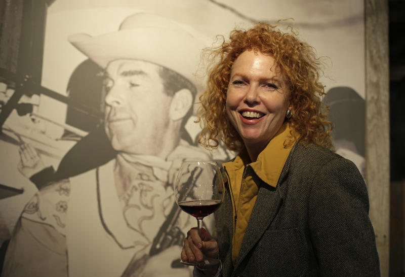 """In this photo taken March 15, 2013 Kate MacMurray, daughter of the late actor Fred MacMurray poses with a glass of Pinot Noir by a photograph of her father in a tasting area and gallery of old photographs at the MacMurray Ranch in Healdsburg, Calif. The former cattle ranch, which was purchased in 1941 by the actor in the popular TV series """"My Three Sons,"""" now produces wine and is owned by the Gallo wine family. (AP Photo/Eric Risberg)"""
