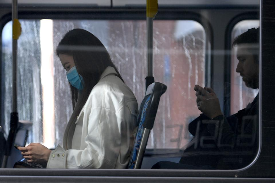 Two commuters on a Sydney bus, one wearing a face mask.
