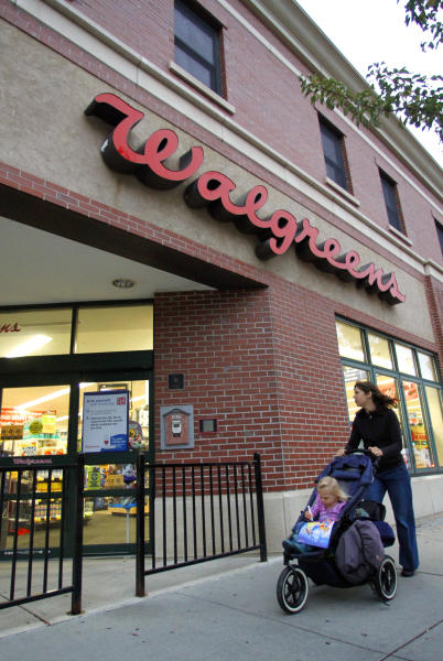FILE - In this Sept. 27, 2010 file photo, a woman pushes a baby carriage past the entrance of a Walgreens pharmacy in Brookline, Mass. Drugstore chain Walgreen Co. says it will spend $6.7 billion to buy a stake in European health and beauty retailer Alliance Boots, the first international venture for the largest U.S. drugstore chain. (AP Photo/Steven Senne, File)