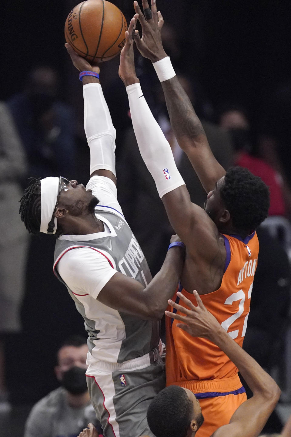 Los Angeles Clippers guard Reggie Jackson, left, shoots as Phoenix Suns center Deandre Ayton defends during the first half in Game 4 of the NBA basketball Western Conference Finals Saturday, June 26, 2021, in Los Angeles. (AP Photo/Mark J. Terrill)