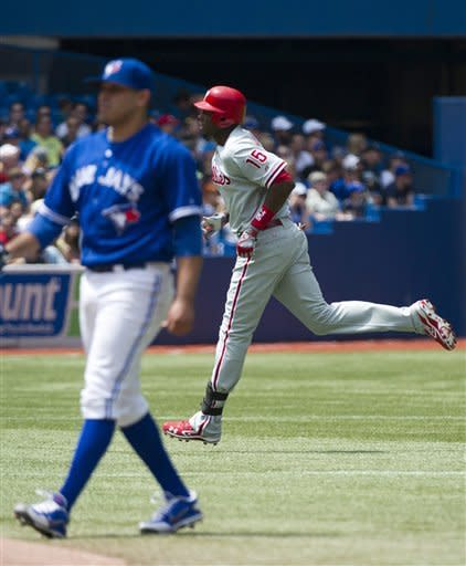 Philadelphia Phillies left fielder John Mayberry Jr., right, rounds the bases on his three-run home run past Toronto Blue Jays starting pitcher Ricky Romero, foreground left, during the third inning of an interleague baseball game in Toronto on Saturday, June 16, 2012. (AP Photo/The Canadian Press, Nathan Denette)