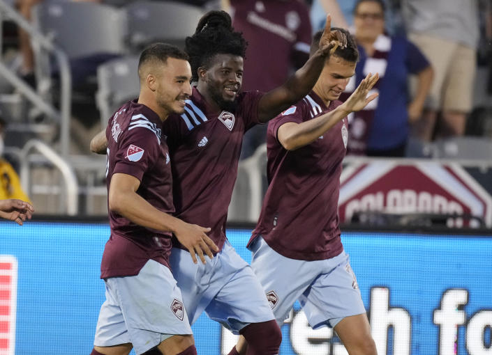 Colorado Rapids defender Lalas Abubakar, center, is congratulated on his goal by forward Andre Shinyashiki, left, and midfielder Cole Bassett during the second half of the team's MLS soccer match against FC Dallas on Wednesday, July 21, 2021, in Commerce City, Colo. The Rapids won 2-0. (AP Photo/David Zalubowski)