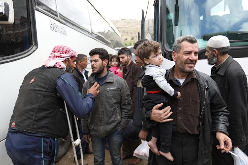 Syrian civilians and rebel fighters arrive in Hama province on March 25, 2018, after being evacuated from Eastern Ghouta following an evacuation deal brokered by regime backer Russia (AFP Photo/OMAR HAJ KADOUR)