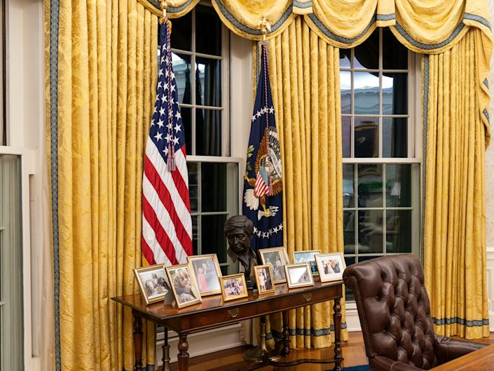 A table with family photos behind Joe Biden's desk in the Oval Office of the White HouseAP