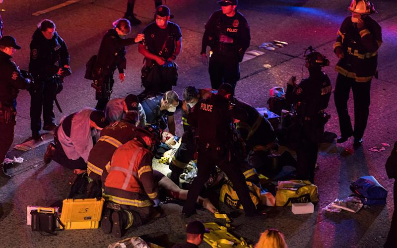 Emergency workers tend to one of the injured people on the ground after a driver sped through a protest-related closure on the Interstate 5 freeway in Seattle - James Anderson