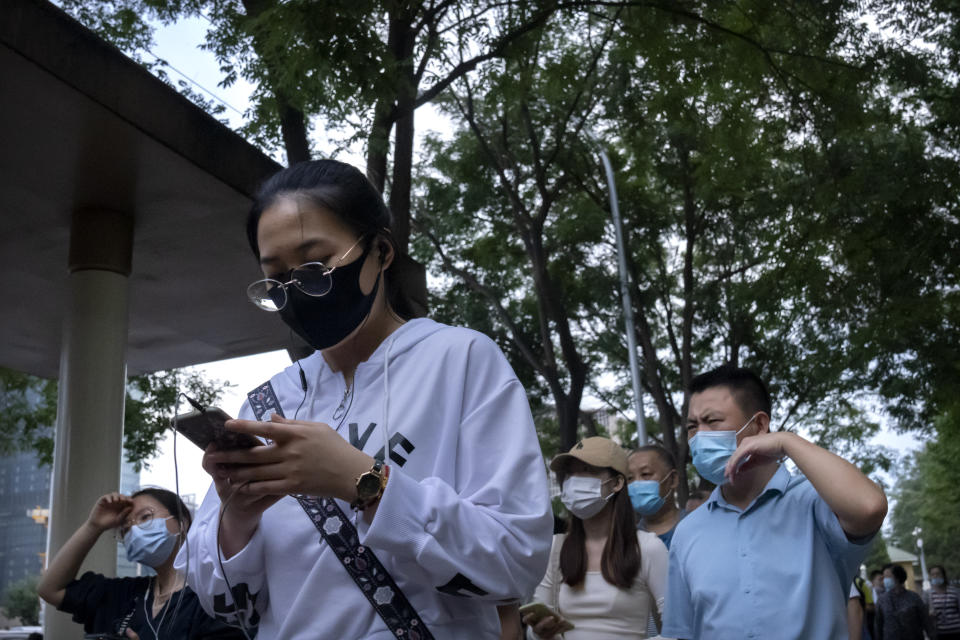People wearing face masks to protect against COVID-19 wait in line at a bus stop in the central business district in Beijing, Thursday, Sept. 16, 2021. China on Thursday reported several dozen additional locally-transmitted cases of coronavirus as it works to contain an outbreak in the eastern province of Fujian. (AP Photo/Mark Schiefelbein)
