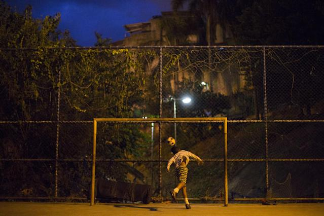 In this Monday, June 2, 2014 photo, a youth tries to block a ball during a soccer game in the Mangueira slum of Rio de Janeiro, Brazil. Less than half a kilometer separates the slum from Maracana stadium, but slum residents will be following the World Cup on television due to the expense. (AP Photo/Leo Correa)