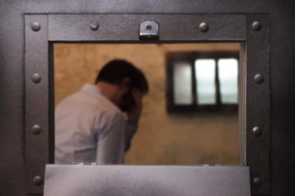 A man stands in a prison cell by a barred window, his head in his hand.