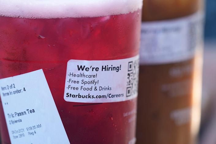 A sticker offering jobs adorns the side of a tea at a Starbucks Thursday, Oct. 7, 2021, in Sioux Falls, S.D.