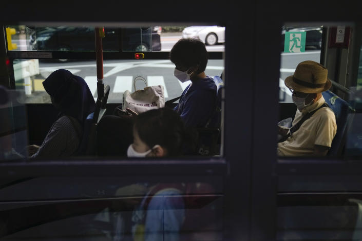 Commuters sit in a bus ahead of the 2020 Summer Olympics, Friday, July 16, 2021, in Tokyo. (AP Photo/Jae C. Hong)