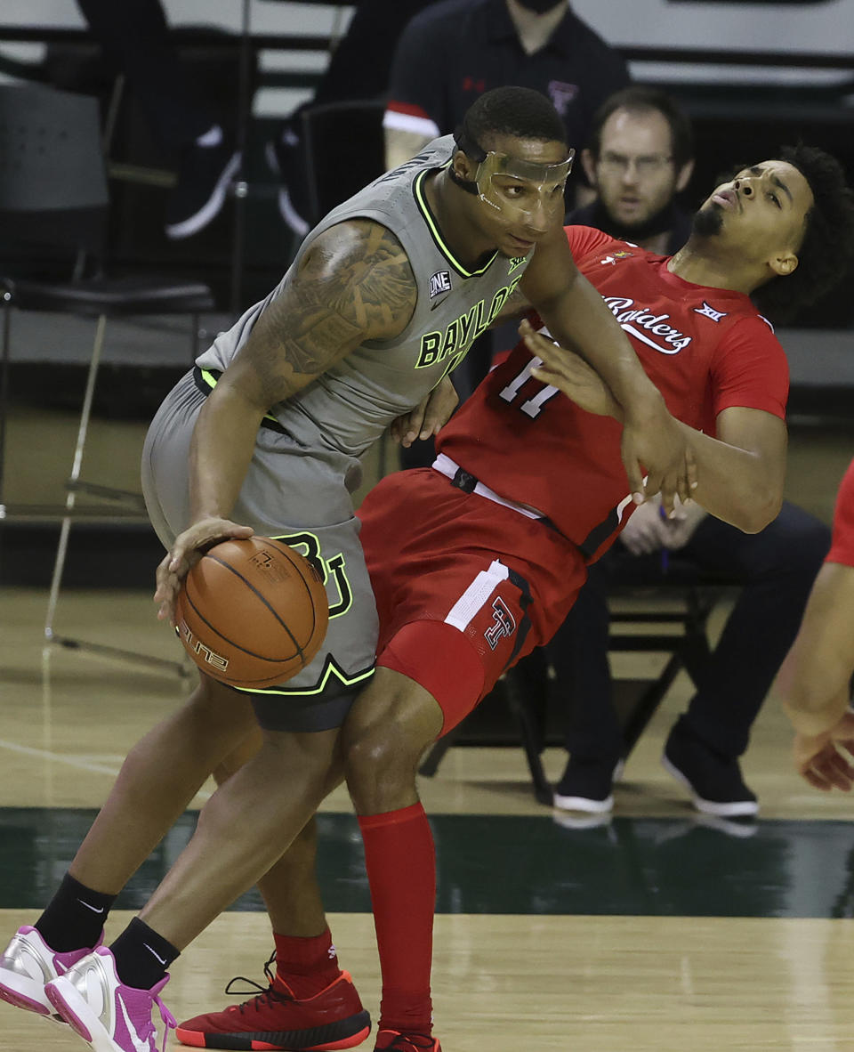 Baylor guard Mark Vital (11) drives the ball past Texas Tech guard Kyler Edwards (11) in the first half of an NCAA college basketball game Sunday, March 7, 2021, in Waco, Texas. (AP Photo/Jerry Larson)