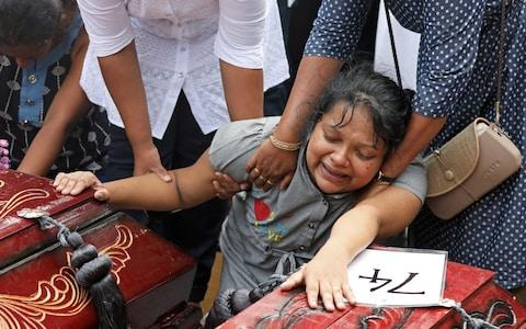Grief stricken relatives collapsed into the arms of bystanders during the mass funeral - Credit:  ATHIT PERAWONGMETHA/REUTERS