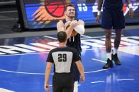 Dallas Mavericks' Luka Doncic, center, grabs the ball after referee Mark Lindsay (29) called a foul against center Willie Cauley-Stein in the second half in Game 3 of an NBA basketball first-round playoff series again the Los Angeles Clippers in Dallas, Friday, May 28, 2021. (AP Photo/Tony Gutierrez)