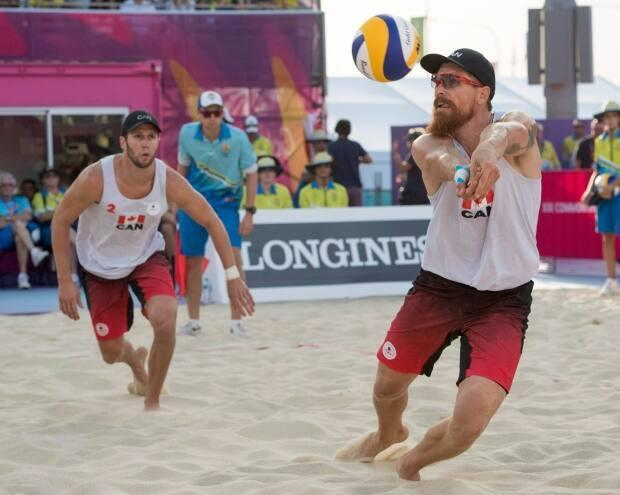 Canada's Samuel Pedlow, right, returns a shot as teammate Sam Schachter looks on during the beach volleyball final against Australia at the Commonwealth Games in 2018. (Ryan Remiorz/The Canadian Press - image credit)