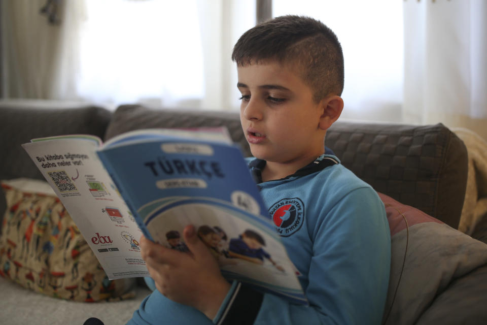 """Amr Sayed Darwish, 10, a Syrian refugee reads a Turkish textbook at home in Istanbul, Friday, Sept. 17, 2021. Fatima Alzahra Shon thinks neighbors attacked her and her son Amr in their Istanbul apartment building because she is Syrian. The 32-year-old refugee from Aleppo was confronted on Sept. 1 by a Turkish woman who asked her what she was doing in """"our"""" country. Shon replied, """"Who are you to say that to me?"""" The situation quickly escalated. (AP Photo/Emrah Gurel)"""