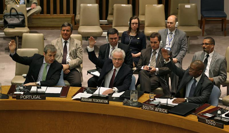 Members of the United Nations Security Council, including Russia's U.N. Ambassador Vitaly Churkin, foreground second from left, raise their hands Saturday, April 14, 2012 at U.N. headquarters during a unanimous vote authorizing the deployment of the first wave of U.N. military observers to monitor a cease-fire between the Syrian government and opposition fighters. (AP Photo/Craig Ruttle)