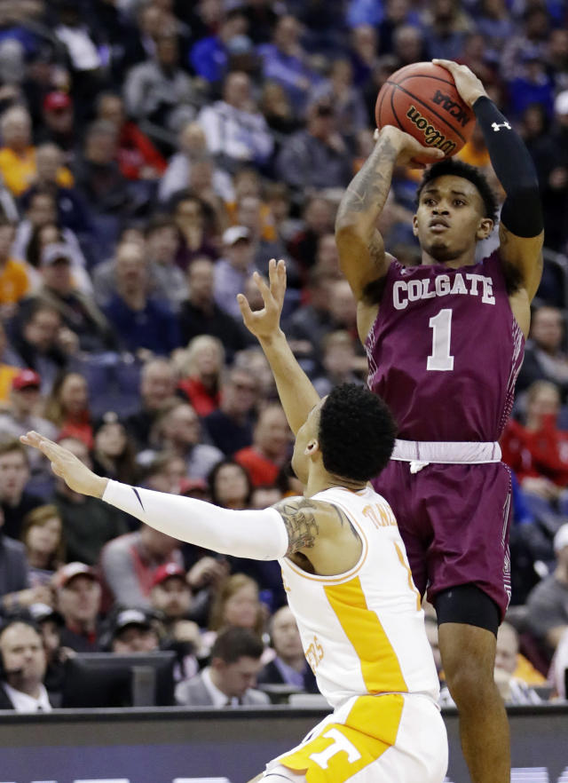 Colgate's Jordan Burns, right, shoots over Tennessee's Lamonte Turner during the first half of a first-round game in the NCAA mens college basketball tournament in Columbus, Ohio, Friday, March 22, 2019. (AP Photo/Tony Dejak)