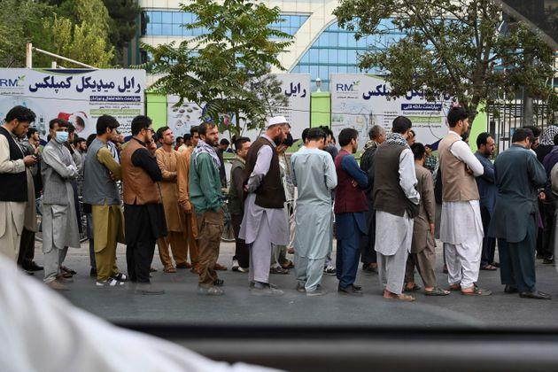 <strong>Afghans queue up as they wait for the banks to open and operate at a commercial area in Kabul.</strong> (Photo: AAMIR QURESHI via Getty Images)