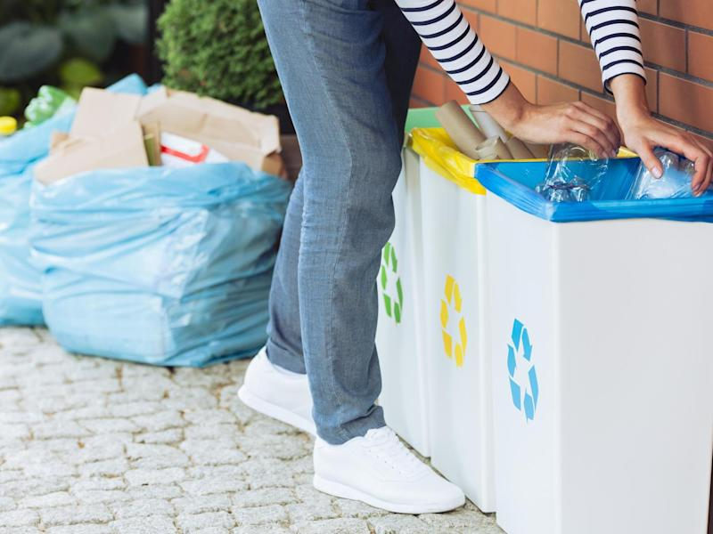 Close-up of person putting plastic bottles into bin with blue symbol (Getty Images/iStockphoto)