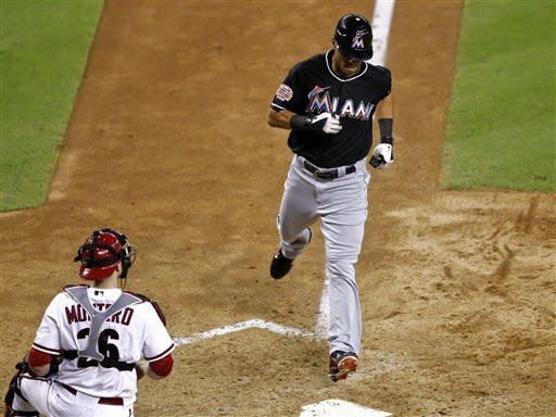 Miami Marlins' Gorkys Hernandez scores on an RBI single by Giancarlo Stanton as Arizona Diamondbacks catcher Miguel Montero watches during the 10th inning of a baseball game, Tuesday, Aug. 21, 2012, in Phoenix. (AP Photo/Matt York)