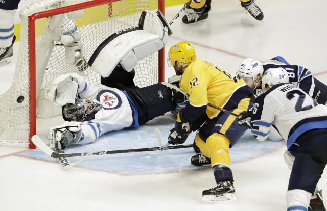 Winnipeg Jets goalie Connor Hellebuyck blocks a shot by Nashville Predators center Mike Fisher (12) during the first overtime in Game 2 of an NHL hockey second-round playoff series, Sunday, April 29, 2018, in Nashville, Tenn. (AP Photo/Mark Humphrey)