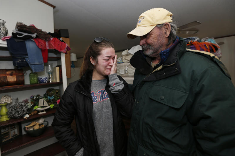 Abby McInnis, 19, cannot suppress her tears at the thought of how anticipated flood waters will affect the home of her grandfather Mark Harvey, right, at the Harbor Pines Mobile Home Community in Ridgeland, Miss., Friday, Feb. 14, 2020. Officials estimate the flooding along the Pearl River may be the worst in the area since 1983. (AP Photo/Rogelio V. Solis)