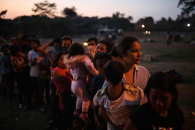 <p>Central American migrant women and children stand in line for food during the annual Migrant Stations of the Cross caravan as the group sets up camp at a sports center in Matias Romero, Oaxaca state, Mexico, late Monday, April 2, 2018. (Photo: Felix Marquez/AP) </p>