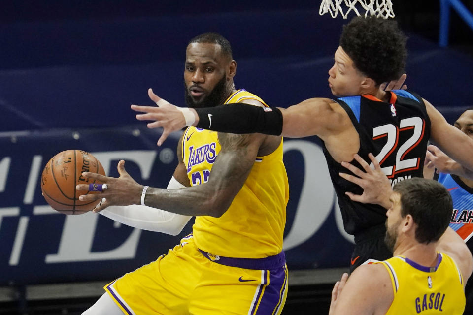 Los Angeles Lakers forward LeBron James, left, moves around Oklahoma City Thunder forward Isaiah Roby (22) during the first half of an NBA basketball game Wednesday, Jan. 13, 2021, in Oklahoma City. (AP Photo/Sue Ogrocki)