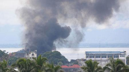 Smoke billows behind a mosque in a residential neighbourhood in Marawi City due to fighting between government soldiers and the Maute militant group, in southern Philippines May 28, 2017. REUTERS/Erik De Castro