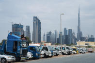 In this Thursday, April 16, 2020 photo, a truck driver works on the cab of his vehicle as Dubai's skyscrapers loom in the background, in Dubai, United Arab Emirates. Migrant workers in oil-rich Gulf Arab states find themselves trapped by the coronavirus pandemic. They are losing jobs, running out of money and desperate to return home as the coronavirus, stalks their labor camps. An unknown number of workers have contracted the virus or have suddenly been forced into mass quarantines, leaving them exposed and painfully vulnerable with little recourse for help. (AP Photo/Jon Gambrell)