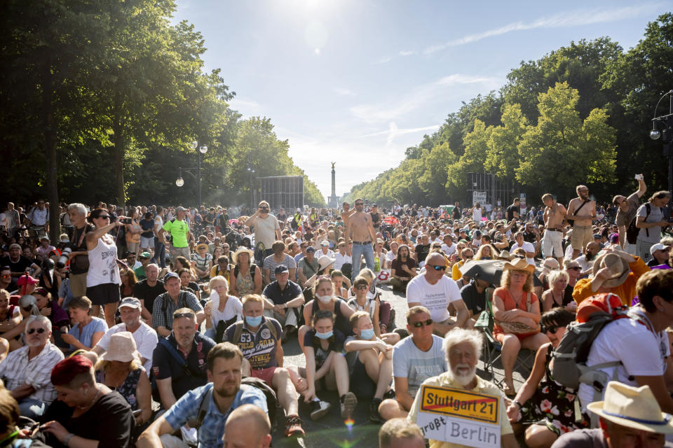 """Protestors sit on the ground after the police declared the end of a protest, in Berlin, Germany, Saturday, Aug. 1, 2020. Thousands converged in Berlin to protest Germany's coronavirus restrictions at a demonstration proclaiming """"the end of the pandemic"""" has arrived. The protest comes as German authorities are voicing increasing concerns about an uptick in new infections. (Christoph Soeder/dpa via AP)"""