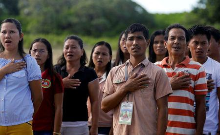 Filipinos living in Philippine occupied (Pagasa) Thitu island, in disputed South China Sea, sing the country's national anthem