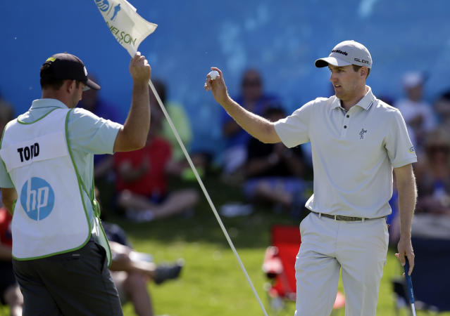 Caddie Steve Lohmeyer, left, replaces the pin in the cup as Brendon Todd acknowledges applause from the gallery after sinking a putt for birdie on the 17th green during the second round of the Byron Nelson Championship golf tournament, Friday, May 16, 2014, in Irving, Texas. Todd finished the round at 8-under par. (AP Photo/Tony Gutierrez)